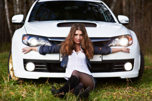 Beautiful girl and stylish white sports car on nature