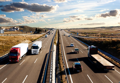 International shipment, trucks and cars driving on the road.Logistics and warehousing
