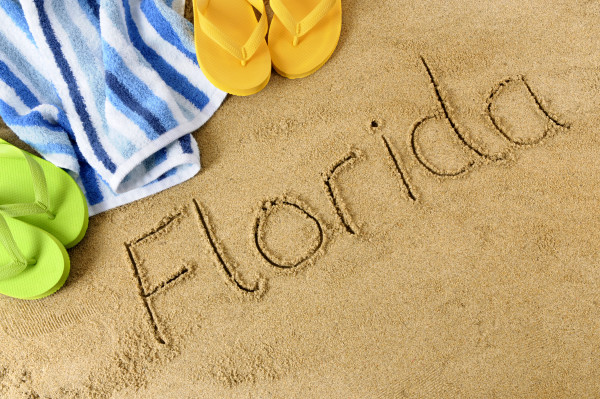The word Florida written in sand with flip flops and beach towel